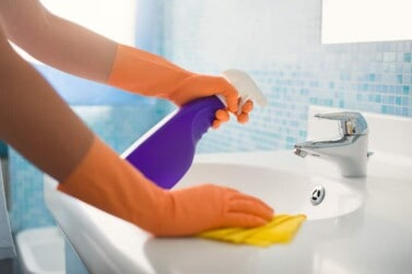 woman cleaning bathroom at home, cleaning sink and faucet with spray detergent.