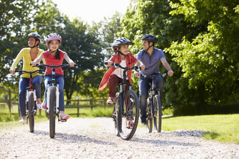 family on bike ride to minimize entertainment spending while facing budgeting challenges