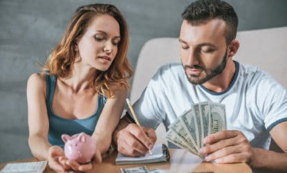 Couple budgeting their money at the table as they begin to manage their money better and stop living paycheck to paycheck.