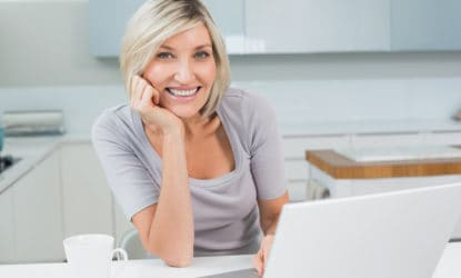 Portrait of a casual young woman with coffee and laptop in the kitchen at home