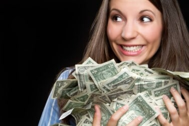 Beautiful smiling woman holding money after earning cash back with Paribus