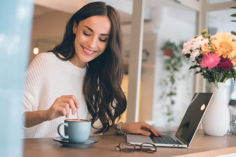 smiling woman stirring mug of coffee while holding her other hand on a laptop with colorful flowers nearby
