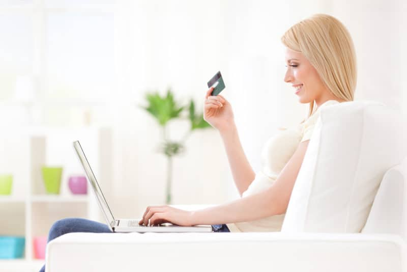woman sitting on a couch shopping online with credit card