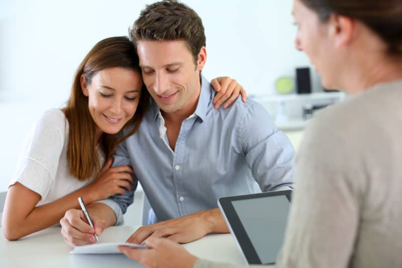Smiling young couple signing real-estate contract