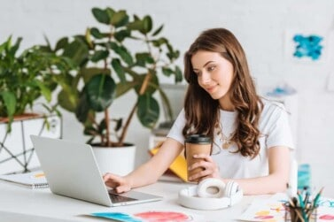Smiling Young Woman Using Laptop Holding Paper Cup While Sitting and Working on her Online Jobs