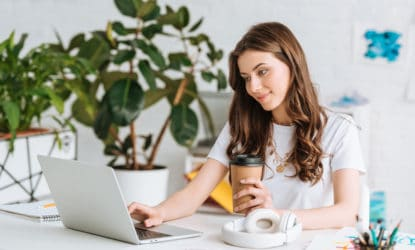 Smiling Young Woman Using Laptop Holding Paper Cup While Sitting and Working on her Online Job