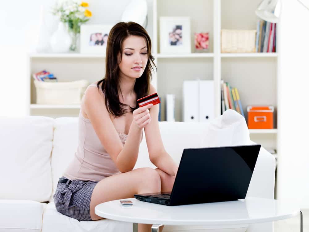 woman sitting at laptop computer with credit card ready to get starting making money on shopify