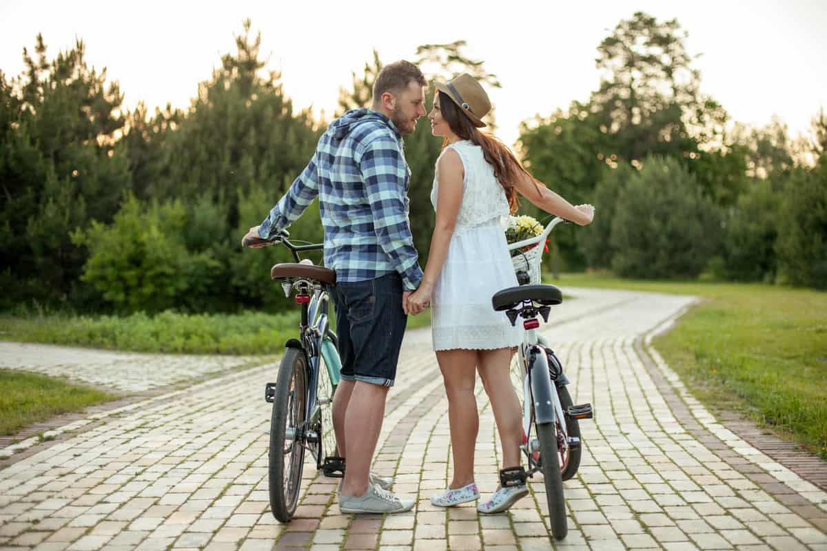 Cheerful man and woman are falling in love. They are riding bicycles. Lovers are holding hands and looking at each other with passion. They are smiling happily
