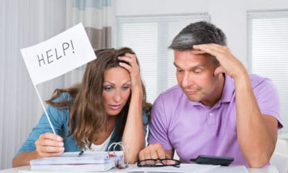 Worried Couple Sitting In Living Room Needs Help Due To Financial Crisis