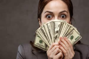 Woman holding money she made from her quick side hustle