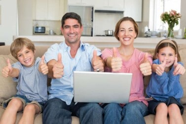 Portrait of happy family with laptop showing thumbs up sign while sitting on sofa at home
