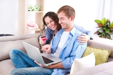 Young couple with Laptop and Credit Card viewing their credit score