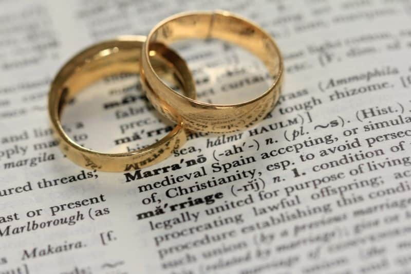 two gold wedding rings laying on a dictionary at the definition for marriage
