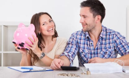 Young Man Looking At Woman Inserting Coin In Piggybank to start their 52-week money saving challenge