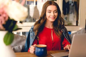 Beautiful woman wearing a red sweatshirt at a coffee shop making money with online surveys