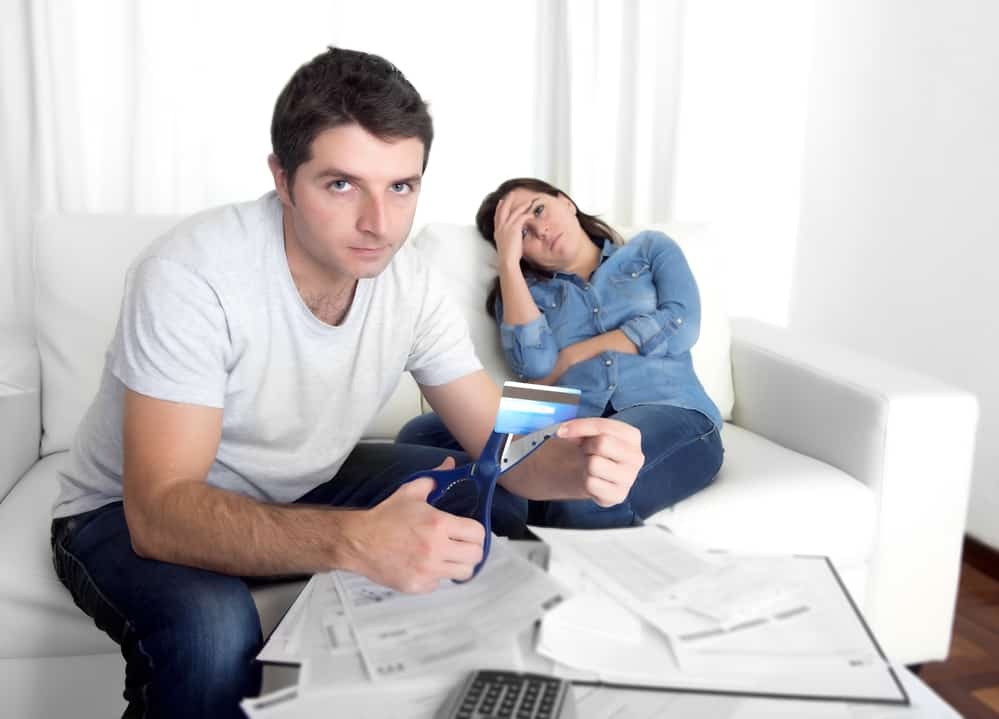 couple cutting credit cards to avoid living beyond your means