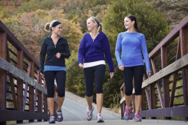 Three beautiful moms walking across a bridge while they are getting paid to walk