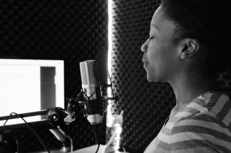 woman with closed eyes singing into a microphone in a recording studio