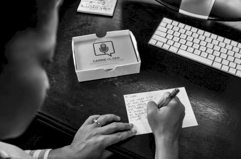 woman writing on a notecard at her work desk with business cards nearby