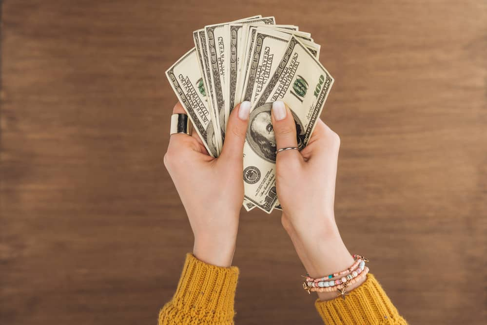 woman holding cash saving money with alternatives to cable tv