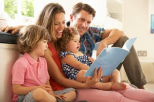 Parents Sitting With Children Reading Story Indoors