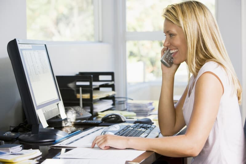 Woman in home office with computer using telephone smiling starting a side hustle as a money hack