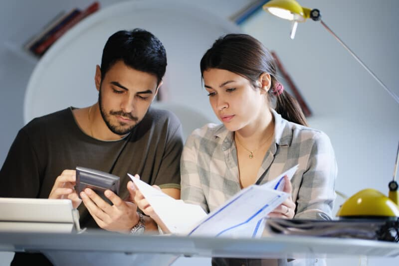 young couple looking at notebook and calculator making money moves to organize their financial life