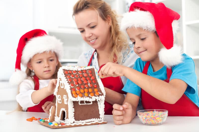 mother and children making gingerbread house new christmas on a budget tradition