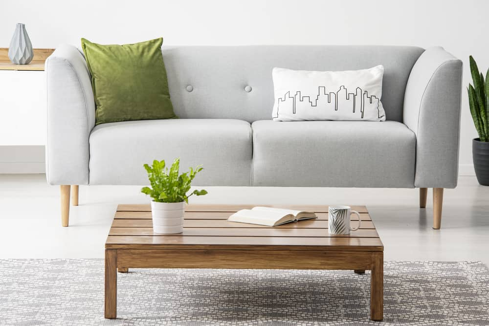 Simple, wooden coffee table in front of a gray settee with fashionable pillows in a monochromatic living room interior