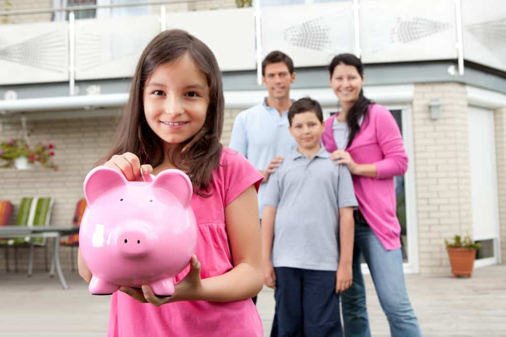 Beautiful little girl inserting coin in a piggy bank with her family in background