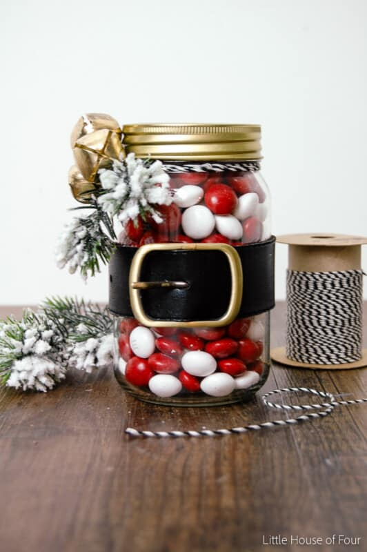 mason jar with belt and filled with red and white candy