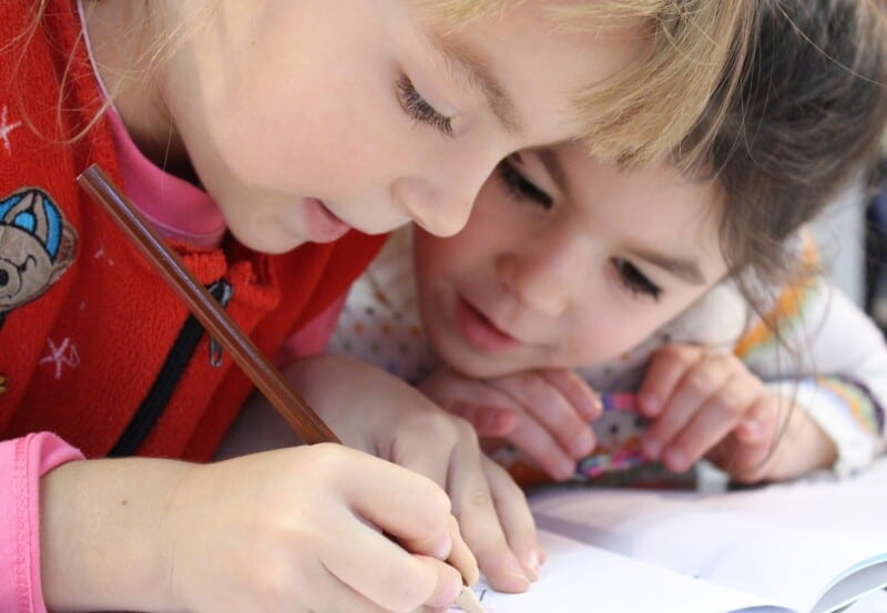 two little girls working over a notebook on their budget while they learn about credit cards