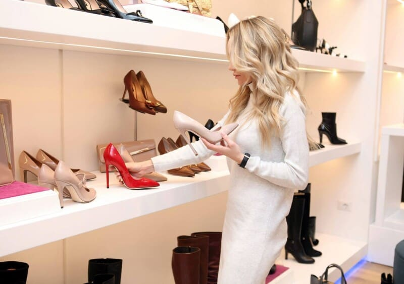 woman carefully considering between pairs or shoes to practice simple living and only purchase items she loves