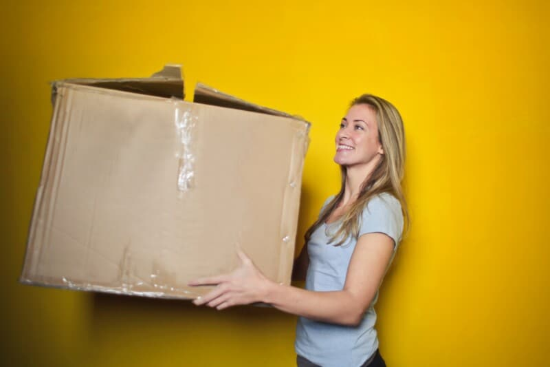 woman carrying donations box to declutter and simplify living