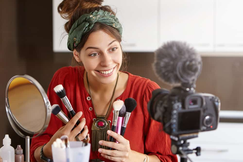 Cosmetology and online video translation concept. Female cosmetologist blogging before breakfast, having her personal online journal in internet, making photos for it while using camera with tripod