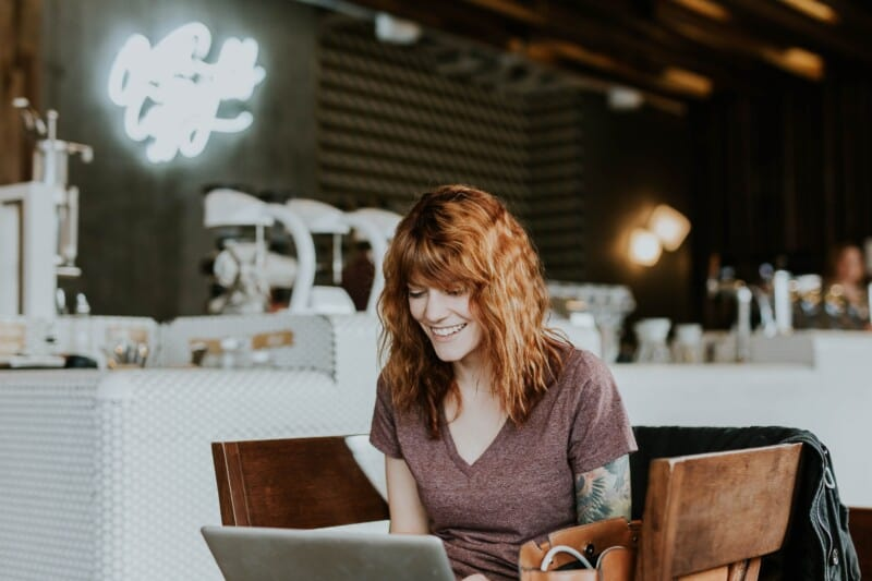 woman at a cafe smiling while doing pinterest VA work
