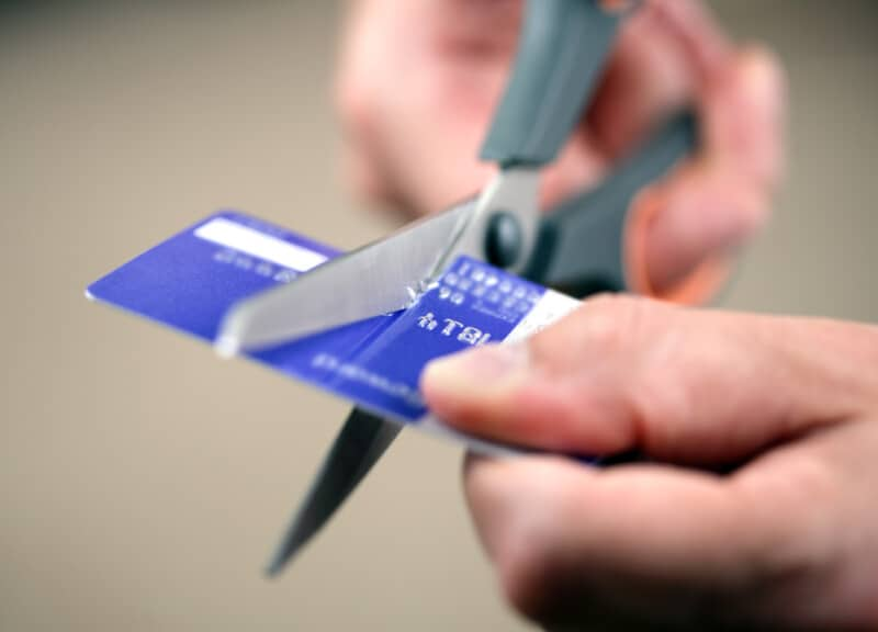Hands cutting a credit card with scissors to protect credit score