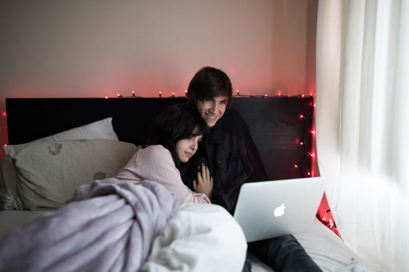 young couple snuggling under a blanket to watch free movies online from their laptop