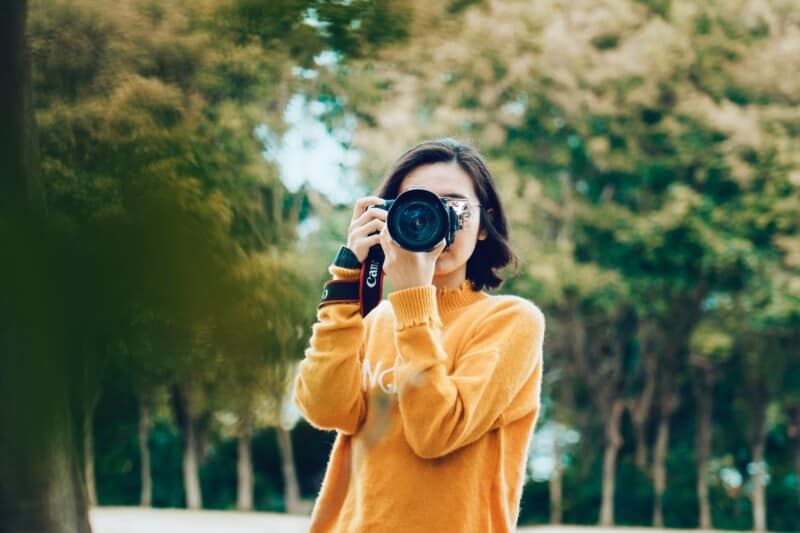 woman holding profressional camera taking photo