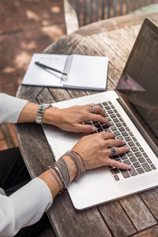 woman typing on a laptop starting a small business blog