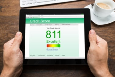 person holding a tablet showing a credit score
