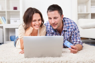 Happy Young Couple Shopping Online Using Laptop And Credit Card
