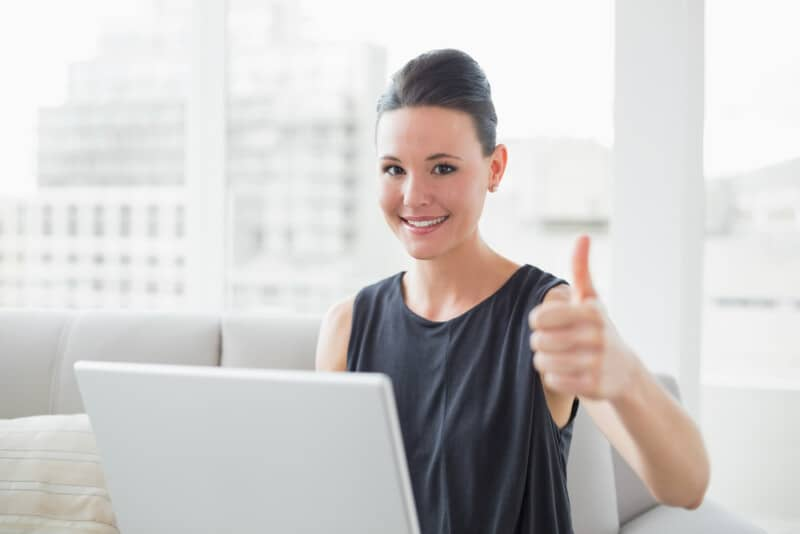professional woman giving thumbs up after investing in an online business for a passive income idea