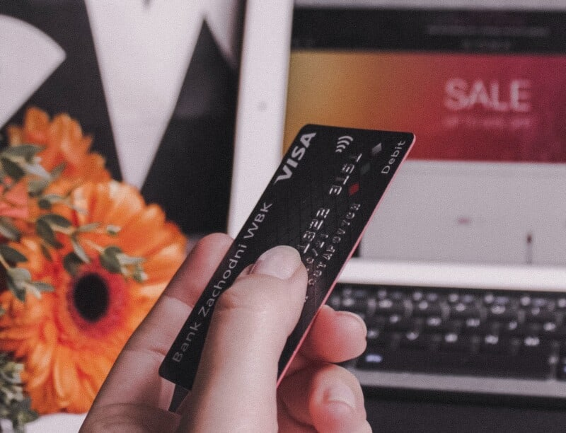 woman holding credit card wondering about credit score vs fico score