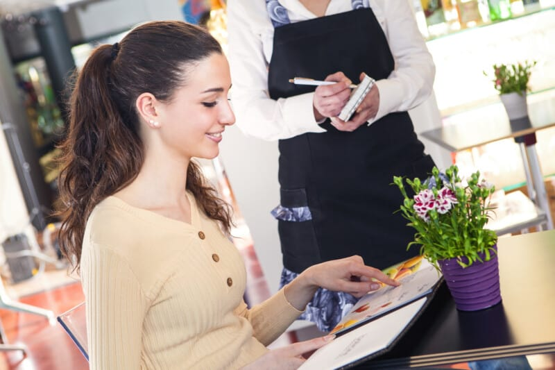 young woman ordering at a restaurant doing mystery shopper job