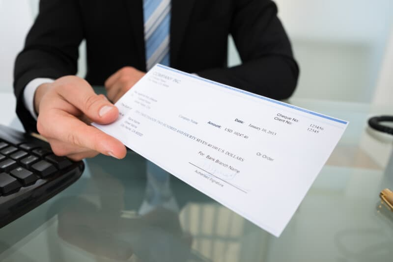 boss handing over paycheck making employee need check cashing near me