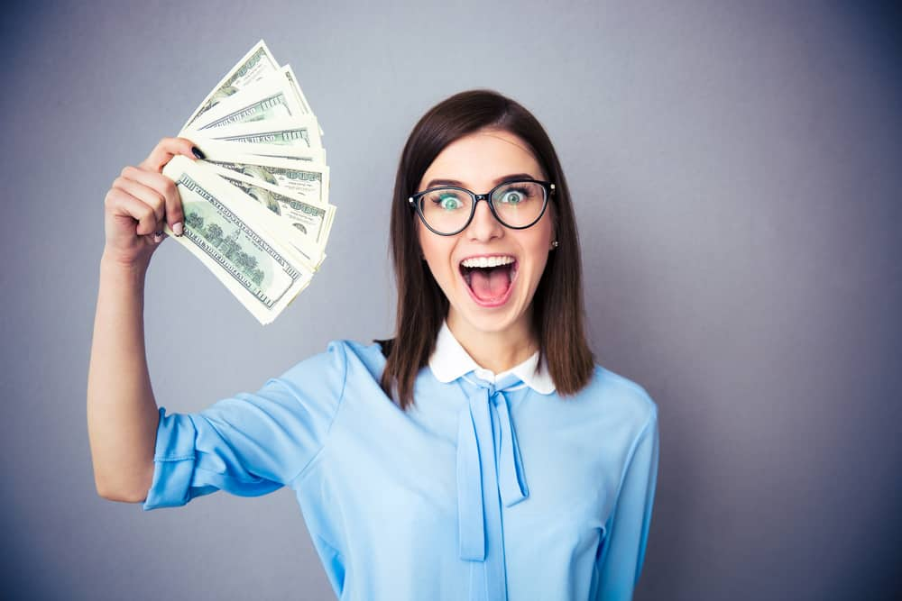 happy professional woman holding cash earned after answering why start a blog