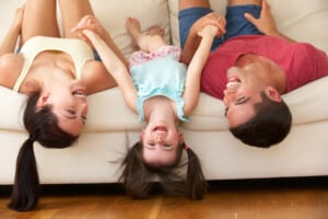 Family Lying Upside Down On Sofa With Daughter