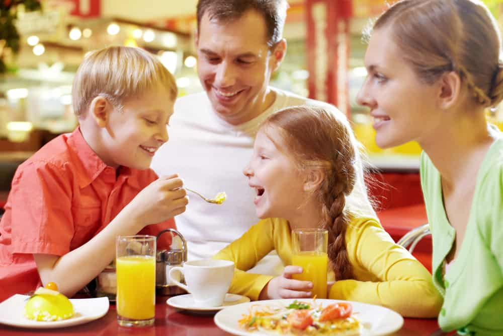 Family with two children sitting in café, the boy feeding his sister with spoon