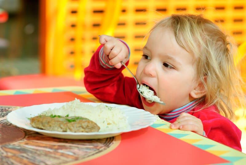 toddler eating dinner at restaurant where kids eat free